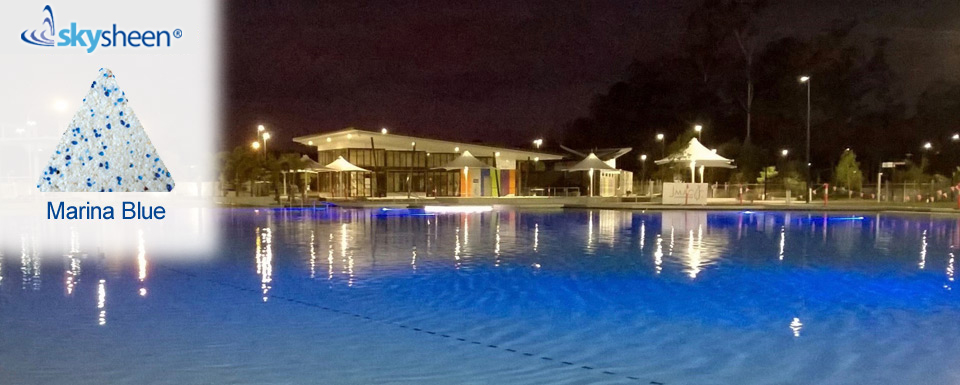 Commercial pool at night with Skypebble®'s Marina Blue Pebblesheen® finish
