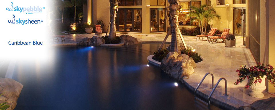 Landscaped backyard swimming pools with Caribbean Blue Skypebble® finish