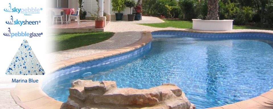Landscaped backyard swimming pools with Marina Blue Skypebble® finish