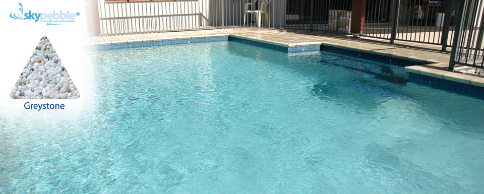 Skypebble®'s Greystone pebble finish in backyard swimming pool